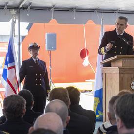 Jeffery Hutchinson, commissaire de la Garde côtière canadienne, prend la parole devant un auditoire assis, sous une tente blanche. Une femme portant l'uniforme de la Garde côtière canadienne se tient à sa gauche, à côté du drapeau de la Garde côtière.