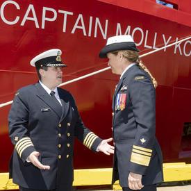 La Capitaine Catherine Lacombe, commandante du NGCC Captain Molly Kool, serre la main de la gouverneure générale Julie Payette devant le navire Captain Molly Kool. Les deux femmes portent l'uniforme de la Garde côtière canadienne.