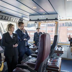 Un groupe de 4 personnes dont la Gouverneure générale Julie Payette écoute un représentant de la Garde côtière canadienne, à l'intérieur du poste de pilotage du navire Captain Molly Kool.