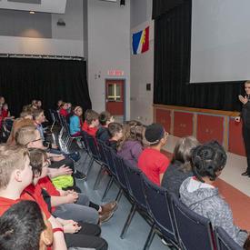 Un groupe d'élèves de la 1re à la 6e année sont assis sur des chaises devant la gouverneure générale Julie Payette, lors d'une présentation PowerPoint.