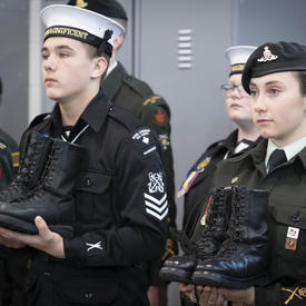 Des cadets tiennent des bottes dans leurs mains.