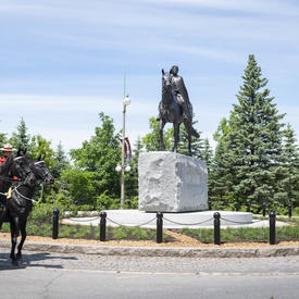 The horses from the RCMP Musical Ride are standing beside the Queen Elizabeth II Equestrian Monument.
