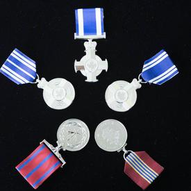 Une photo des différentes médailles remises aux récipiendaires lors de la cérémonie d'honneur à thème militaire.