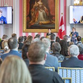 Une photo de la salle pendant la cérémonie, avec la gouverneure générale prenant la parole à la tribune, affichée sur deux écrans.