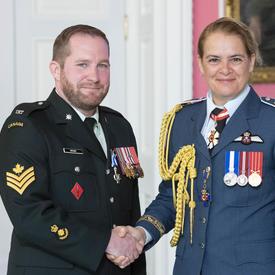 Le caporal-chef Archer serre la main de la gouverneure générale après avoir reçu sa médaille.