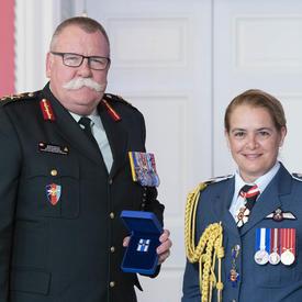 Le brigadier-général Anderson accepte sa médaille de la gouverneure générale et pose pour une photo.