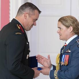 Le colonel Huet accepte sa médaille et serre la main de la gouverneure générale.