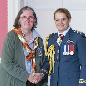 Sally Goddard accepte sa médaille et serre la main de la gouverneure générale.