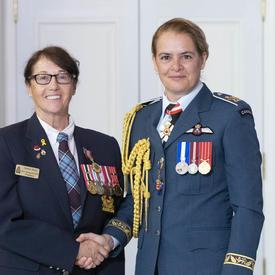 Debra Reid accepte sa médaille et pose pour une photo avec la gouverneure générale.