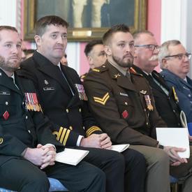 Les récipiendaires de la cérémonie à thème militaire sont assis dans la première rangée et regardent les autres récipiendaires se faire décerner.