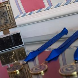 Le trophée du Prix Michener et les trois médailles du Prix Michener, avec des rubans bleus, sont posés sur une table en miroir.