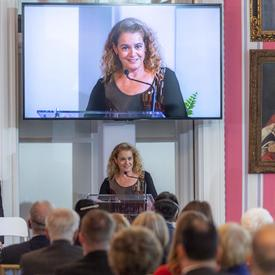 La gouverneure générale est à une tribune et prononce un discours. Un grand écran de télévision est au-dessus d'elle et la montre sur le podium. Un aide-de-camps est à sa droite. Le mur derrière elle est rayé rouge et blanc.