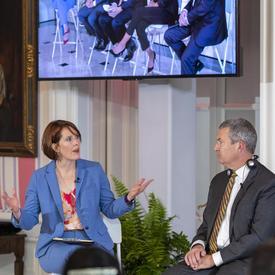 Alison Crawford, vêtue d'un complet bleu, est assise sur un grand tabouret blanc, parlant à David Akin, portant un costume gris et assis sur un grand tabouret blanc. Un grand écran de télévision au-dessus d'eux montre un panel de 5 personnes.