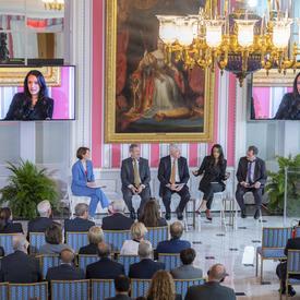Un panel de 5 personnes est assis sur de hauts tabourets devant un auditoire. Deux grands écrans de télévision sont au-dessus d'eux, à leur gauche et à leur droite, sur un mur rayé rouge et blanc.