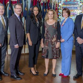 Un groupe de 5 personnes pose pour une photo avec la Gouverneure générale Julie Payette devant les drapeaux.