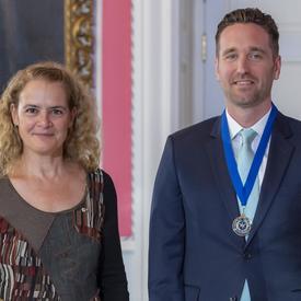 La gouverneure générale du Canada Julie Payette et la journaliste Corbett Hancey, portant une médaille avec un ruban bleu, regardent directement l'appareil photo.