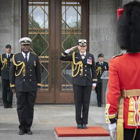 La gouverneure générale, avec l'aide de camp à ses côtés, salue la Garde de cérémonie et le commandant.