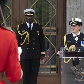 La gouverneure générale prononce un discours à une tribune avec son aide de camp à ses côtés.