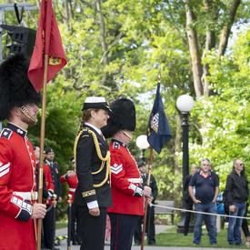 La gouverneure générale se tient entre deux gardes qui observent la Garde de cérémonie avec une admiration silencieuse.