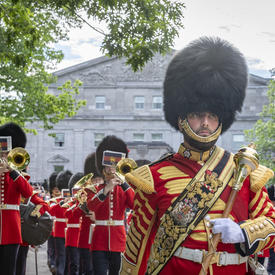 The Band of the Ceremonial Guard marches away from the Rideau Hall entrance while providing musical support.