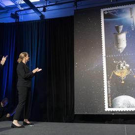 La gouverneure générale applaudit sur scène alors que les timbres Apollo 11 sont dévoilés.