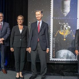 La gouverneure générale pose pour une photo sur scène parmi les cadres supérieurs à côté des timbres Apollo 11.