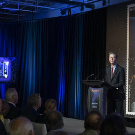 Mr. Ettinger delivers remarks at a podium.