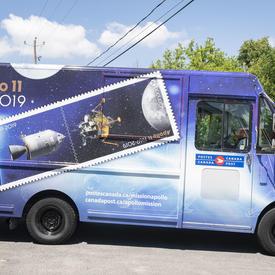 Photo d'un camion de Postes Canada peint avec le dessin Apollo 11.