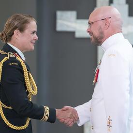 Le premier maître de 1re classe Daniel Eugene Campbell serre la main de la gouverneure générale.