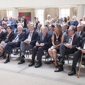 Les invités présents applaudissent et félicitent les membres nouvellement investis de l'Ordre du Canada.