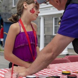 A child getting her face painted.