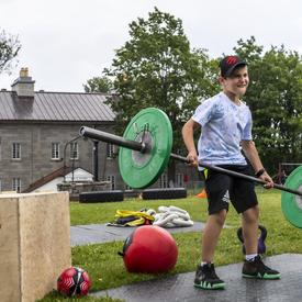 A child is lifting weights as part of an obstacle course.