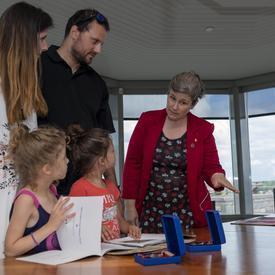 Une famille se renseigne sur le système d'honneur du Canada.