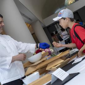 Rideau Hall's Executive Chef handed a snack to a young boy.