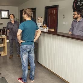 La gouverneure générale discute avec les propriétaires et les employés du Verger Poméloi à l'intérieur, à côté du comptoir d'accueil.