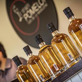 Une photo de bouteilles de cidre Verger Poméloi alignées, scellées et prêtes pour la distribution.