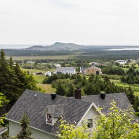 A photo of a white and grey manor at the Verger Poméloi hidden behind trees, land and mountains in the distance.