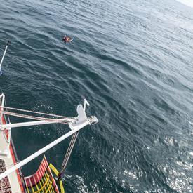 Une photo du NGCC Baie de Plaisance et de son équipage en mer effectuant une démonstration de recherche et sauvetage.