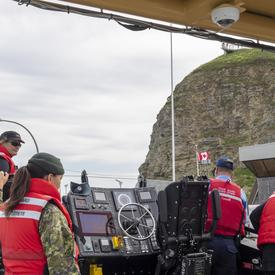 A photo of the CCGS Baie de Plaisance and crew at sea performing a search and rescue demonstration.