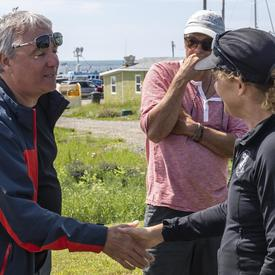 The Governor General meets and shakes hands with a local resident at Île d'Entrée.