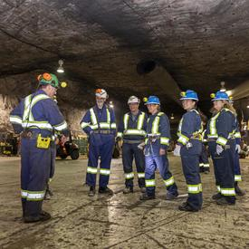 The Governor General is talking with employees from the mine.