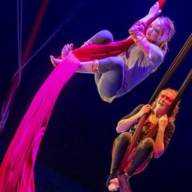 Two girls swing from silk acrobatic ropes.