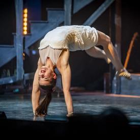 A woman performs acrobatics.