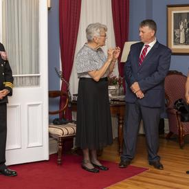 (Left to Right) a photo of an officer, Her Honour the Honourable Antoinette Perry, the Honourable Dennis King, and Her Excellency the Right Honourable Julie Payette, inside Government House.