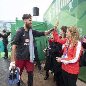 La gouverneure générale a salué Aaron Nusbaum et Mike Plantinga, deux joueurs masculins de volley-ball de plage du Canada, après le match.