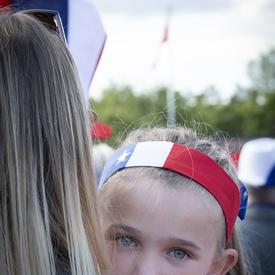 Une jeune fille vêtue des couleurs nationales acadiennes est dans les bras de sa mère.