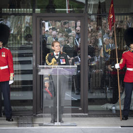 The Governor General delivers remarks at a podium, two ceremonial guards standing solemnly on either side.