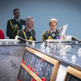The Governor General and the Chief of the Defence Staff examine the Kandahar Cenotaph and read from an archival book.