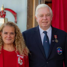 The Governor General takes a photo with a medal recipient.