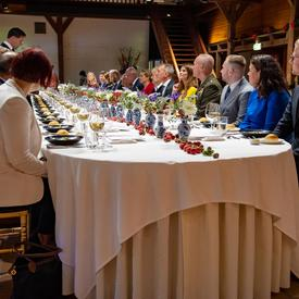 The Governor General sits among guests at a long table during a luncheon hosted by Prime Minister Rutte.